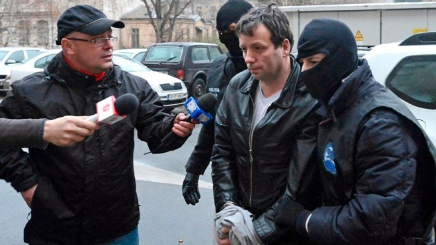 Jan. 22, 2014: Marcel Lazar Lehel, 40, is escorted by masked policemen in Bucharest, after being arrested in Arad, 337 miles west of Bucharest.  (Reuters)