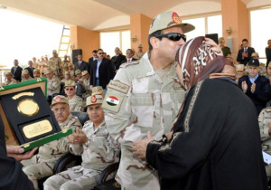 Handout picture of al-Sisi kissing the mother of an army officer, who was killed during the recent Egypt uprising, during the graduation ceremony of a new batch of non-commissioned officers at the NCOs' Institute in Cairo