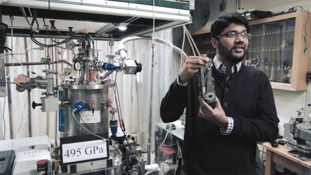 Ranga Dias stands in front of the experimental set-up
